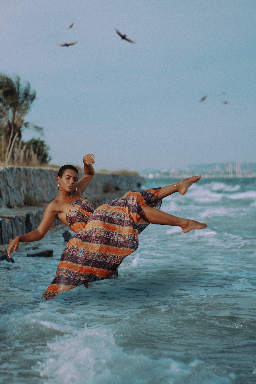 woman with a pixie cut falling into sea with flowing dress on looking relaxed